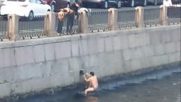 Видео: мужчина водних трусах неможет вылезти изреки вцентре Санкт-Петербурга